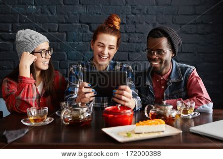 Multiethnic Group Of Three Young People Enjoying Online Communication, Using Free Wi-fi On Generic T