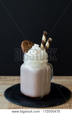 Portion of homemade hot chocolate with whipped cream cookies and wafer sticks served on black slate board on wooden table