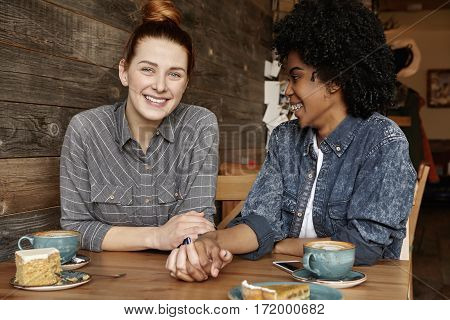 Happy Lesbian Couple Having Date At Cafe. Cute Caucasian Redhead Girl Holding Hands With Her Dark-sk