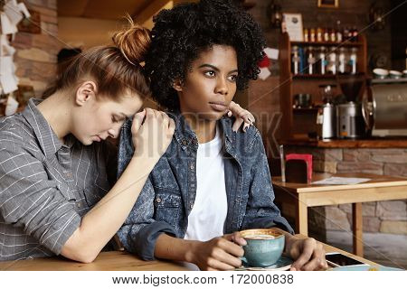 Young Caucasian Female Sitting At Cafe, Saying Sorry, Trying To Apologize To Her Mad And Angry Afric