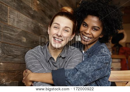 Young Couple Of Same Sex Hugging Tenderly At Cafe. Two Lesbians Having Great Time Together, Embracin