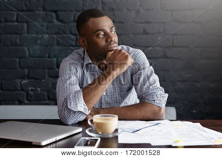 Serious African-american Businessman Having Coffee At Cafe, Sitting At Table With Laptop, Mobile Pho