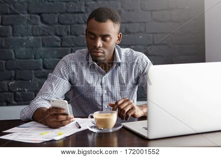 Attractive Young Dark-skinned Entrepreneur Having Serious Look Texting Message On Mobile Phone, Usin