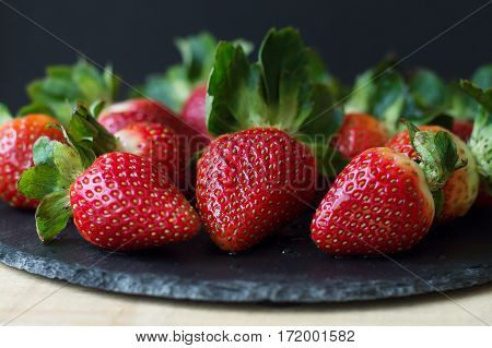 Fresh strawberry on black slate board. Healthy eating concept