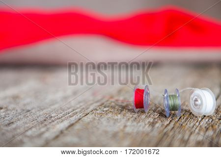 Colorful Sewing Machine Bobbins With Scissors And Black And Red Silky Fabric On A Old Wooden Work Ta