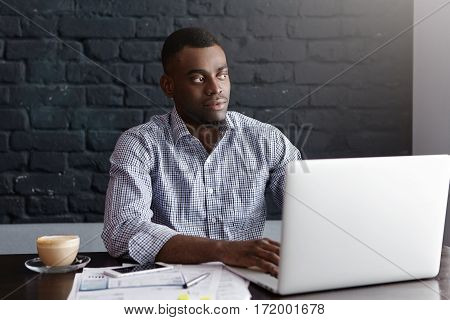 Confident Young African Entrepreneur Sitting In Front Of Open Laptop, Typing Message Online, Using F
