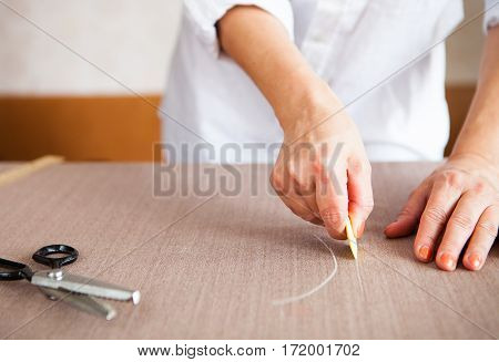 Close Up. Hands Woman Tailor Working Cutting A Roll Of Fabric On Which She Has Marked Out The Patter