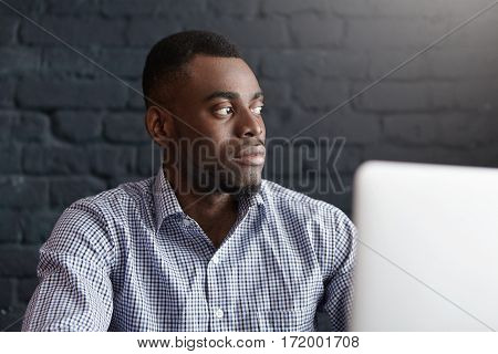 Isolated Shot Of Serious Young Dark-skinned Male Freelancer Wearing Blue Checkered Shirt Using Lapto