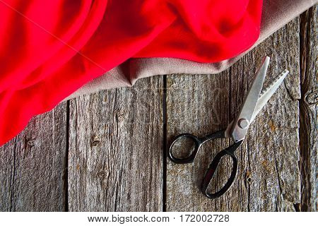 Old Scissors And Red And Brown Fabric On A Old Rustic Work Bench. Tailoring Acsessorises. Flat Lay