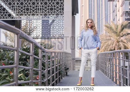 Young business woman with trendy make up curly hairstyle and in smart casual style standing at Dubai street. Positive and confident young female