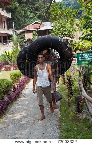 BUKIT LAWANG,INDONESIA - AUGUST 9,2012: Men carry car camera for rafting down the mountain river