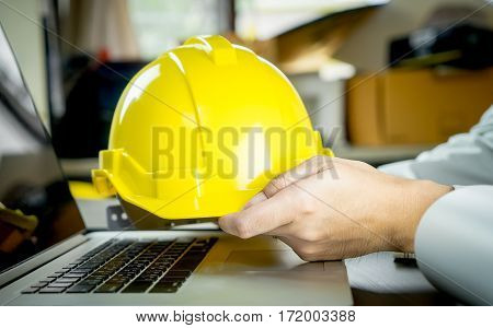 Enigneer is holding yellow safety work helmet in office