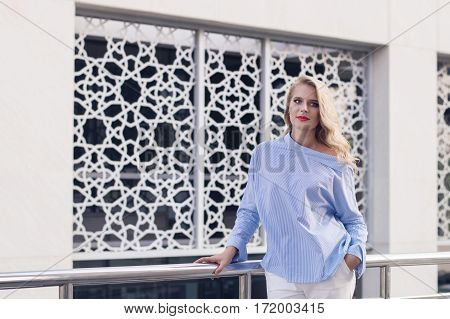 Beautiful european female with long blond hair stand in near white wall with arabic pattern. Young business woman in blue blouse and white trousers