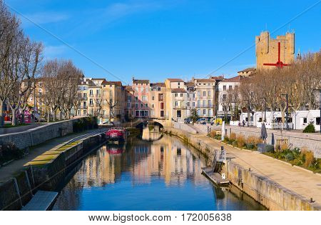 NARBONNE, FRANCE - DECEMBER 27, 2016: The Canal de la Robine channel passing through Narbonne, France, with the Pont des Marchands bridge in the background, one of only two inhabited bridges in France