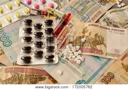 Pills in blister packs vials money background close-up