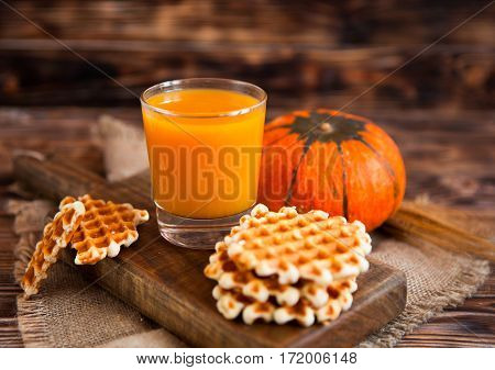 Glass Of Fresh Pumpkin Juice With Wafer And Pumpkin On Dark Wooden Table. Selective Focus.