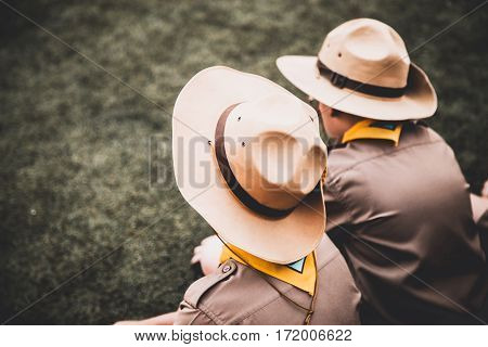 Rear View Or Backside Of Two Asian Boy Scout Sitting On Greensward For Relax Time. Asia Boy Scout Ge