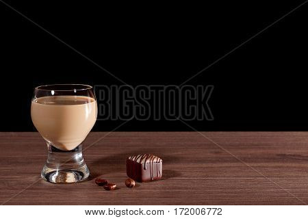 Glass with liquor, candy and coffee beans on a black background. Free space for creativity.