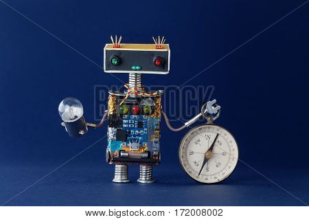 Friendly robot with magnetic exploration compass and light bulb lamp. Navigating looking for journey concept. Blue background. Shallow dept of field