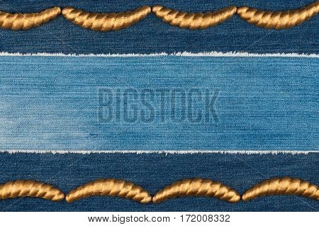 Luxury elegant frame made of gold stucco plaster lying on denim. Copy space. View from above