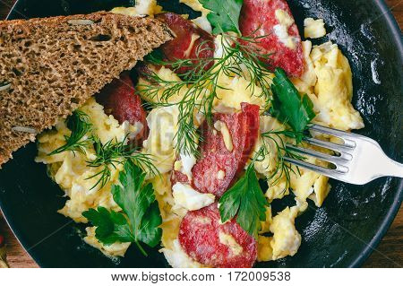 Fresh cooked scrambled eggs in pan with sausage herbs fork and bread close-up top view