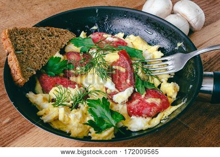 Fresh cooked scrambled eggs in pan with sausage and herbs. Bread fork mushrooms on wooden board
