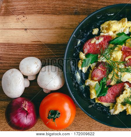 Fresh cooked scrambled eggs in pan with sausage and herbs. Tomato onion mushrooms on wooden board top view