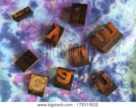 Variety of block printing letters scattered on a dyed fabric background with space for text.