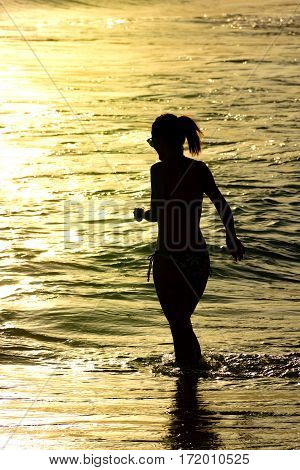 Woman entering the waters of Ipanema beach in Rio de Janeiro during sunset