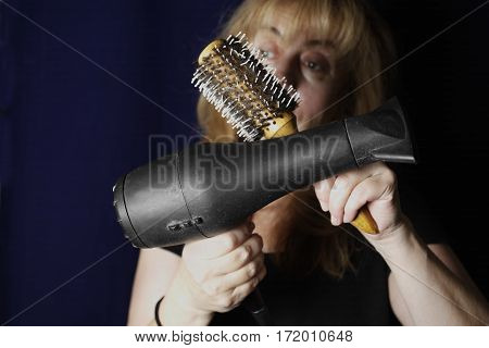 A woman holding a hairdryer and hairbrush in front of her with hands crossed studio cropped shot