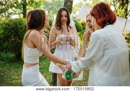 Girls wearing on white dresses having fun on hen party.