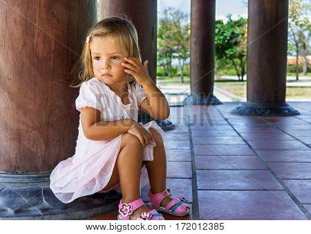 Little Girl Sitting Near The Column