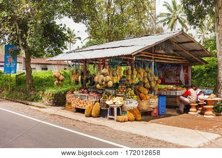 UBUD INDONESIA - January 26 2013. Street fruit shop. Two Balinese sell durians bananas mangosteens.