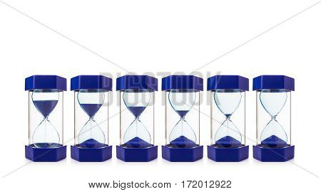 row of six hourglasses on white background showing blue sand dropping from almost full down to completely empty, measure and concept of time, copy spaces, selective focus at the center of hourglass