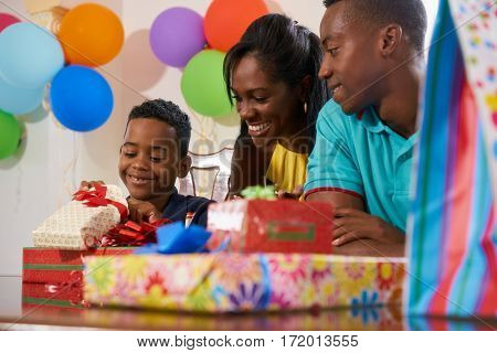 Happy black family at home. African american father mother and child celebrating birthday having fun at party. Young boy opening gifts and smiling.