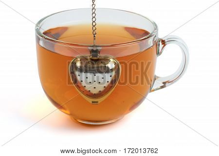 Brewing black tea in the transparent glass cup with heart shape tea strainer. Isolated on white