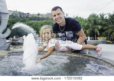 Dad And Daughter Playing. Man Holding A Baby In Arms.