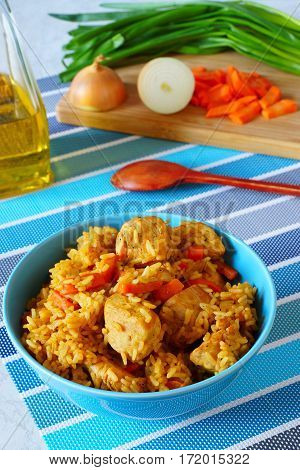 Risotto with chicken. Rice with chicken and vegetables in blue bowl. National dish east. In the background of a cutting board with onions and sliced carrots.