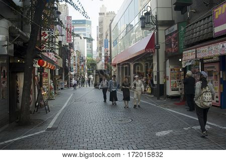 Japanese People And Foreigner Travelers Walking On Street At Small Alley For Work And Travel In Shin