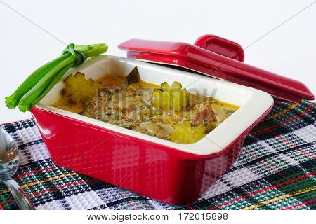 Meat stew with pickles in red ceramic stewpot on plaid kitchen towel.
