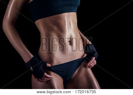 Sporty Female With Perfect Body Against Black Background. Fitness Woman In Sportswear With Ideal Fit