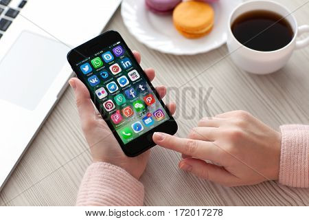 Alushta Russia - November 19 2016: A set of programs from famous brands of social networking on the iPhone 7 in woman hands. iPhone 7 Jet Black was created and developed by the Apple inc.