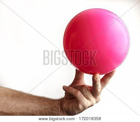 Man's hand holding a ball for gymnastics on a white background