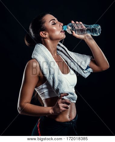 Attractive Athletic Young Woman With Perfect Body Drinking Water From A Bottle With Towel Around Her