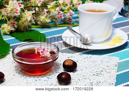 Glass bowl with chestnut honey and a cup of tea on a background of blossoming chestnut branches.