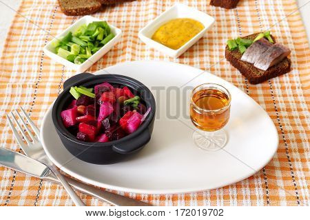 Beetroot salad vinaigrette and a glass of brandy on a white plate. Sandwich with herring, mustard and green onions.