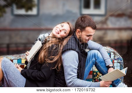 Fashion Of Nice Pretty Young Hipster Woman Is Sitting Back To With A Handsome Man And Reading Book