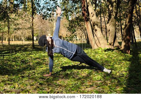 Beautiful girl doing yoga at the park at a sunny day. Vasisthasana side plank pose.
