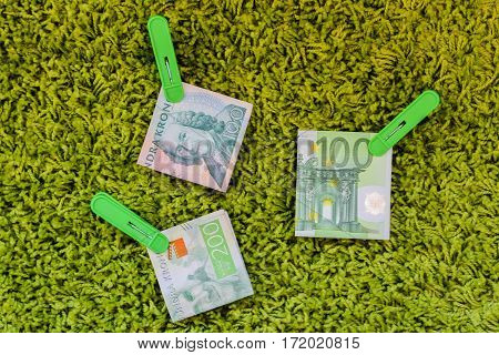 Three green banknotes 100 euro 100 swedish crownes and 200 swedish crownes in green clothes pegs at a green background