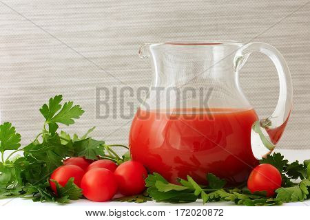 Tomato juice in a glass jug. Cherry tomatoes and parsley. Still life.